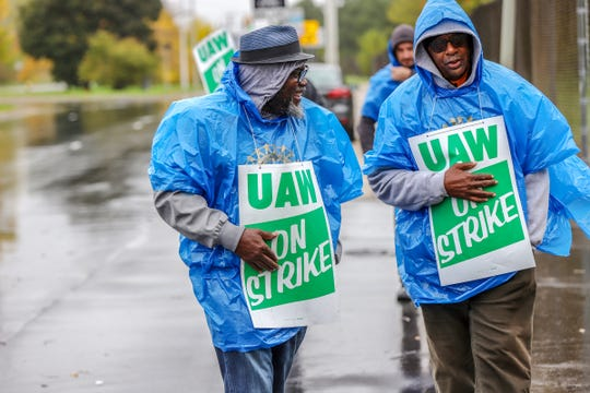 UAW autoworkers Willie Jackson, 63, and Martin Jackson, 68, both of Detroit walk the picket line in front of the General Motors Detroit-Hamtramck assembly plant on Wednesday, Oct. 16, 2019.
