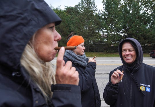 """(Left to right) General Motors Flint Assembly fork truck driver Kim Vovillia, temp material driver Selina Black and material driver Juli Chadwick smoke cigars that Vovillia handed out to some of her co-workers while standing on strike outside of General Motors Flint Assembly on Wednesday, October 16, 2019. """"Almost there. Almost there,"""" Vovillia said after a tentative agreement with GM was reached to possibly end the strike."""