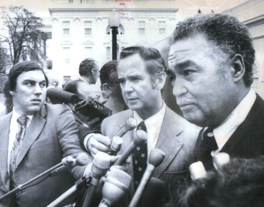 Michigan Gov. William Milliken, center, and Detroit Mayor Coleman Young, right, meet with reporters, outside the White House Wednesday, after conferring with President Ford in April 1975.
