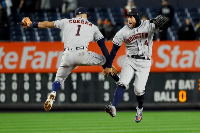 Houston Astros shortstop Carlos Correa, left, and center fielder George Springer celebrate after their 8-3 win Friday  against the New York Yankees in Game 4 of baseball's American League Championship Series.