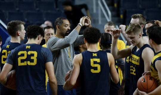 Michigan head basketball coach Juwan Howard, in gray, gathers his team around at the start of practice.