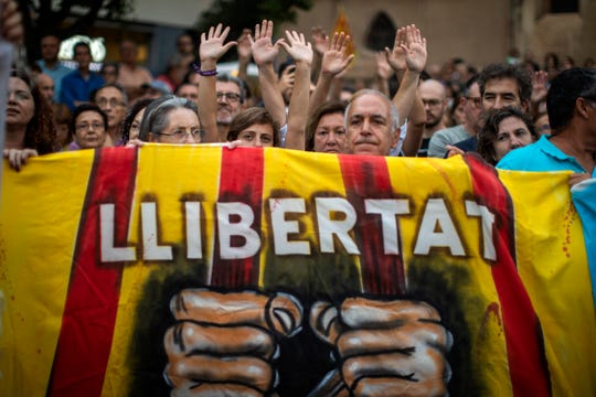 "Pro independence demonstrators hold a banner reading in Catalan ""Freedom"" during a protest condemning the arrest of 9 Catalan activists by Spanish police on Monday, Sept. 23, 2019 in Sabadell, near Barcelona, Spain."