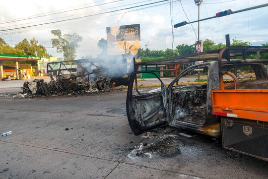 Burnt out vehicles used by gunmen still smolder on a street, a day after street battles between gunmen and security forces in Culiacan, Mexico, Friday Oct. 18, 2019.