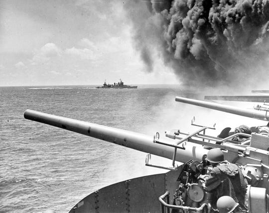In this June 4, 1942 file photo provided by the U.S. Navy the USS Astoria (CA-34) steams by USS Yorktown (CV-5), shortly after the carrier had been hit by three Japanese bombs in the battle of Midway.