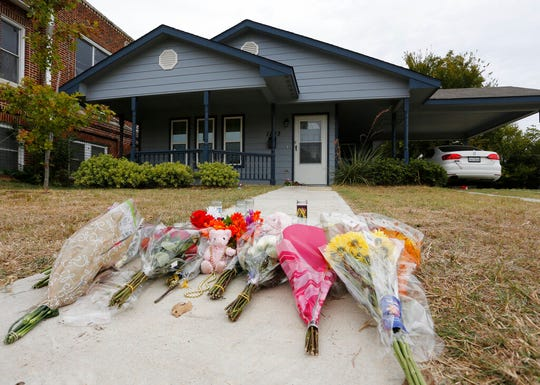 In this Monday, Oct. 14, 2019 photo, flowers lie on the sidewalk in front of the house in Fort Worth, Texas, where a white Fort Worth police officer Aaron Dean shot and killed Atatiana Jefferson, a black woman, through a back window of her home. Dean resigned before he could be compelled to undergo questioning.