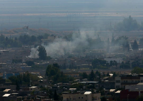 In this photo taken from the Turkish side of the border between Turkey and Syria, in Ceylanpinar, Sanliurfa province, southeastern Turkey, smoke billows from targets in Ras al-Ayn, Syria, caused by shelling by Turkish forces, Friday, Oct. 18, 2019. Fighting continued in a northeast Syrian border town at the center of the fight between Turkey and Kurdish forces early Friday, despite a U.S.-brokered cease-fire that went into effect overnight.