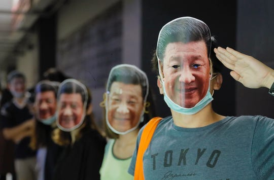 Protesters wear masks of Chinese President Xi Jinping in Hong Kong, Friday, Oct. 18, 2019. Hong Kong pro-democracy protesters are donning cartoon/superheroes masks as they formed a human chain across the semiautonomous Chinese city, in defiance of a government ban on face coverings.
