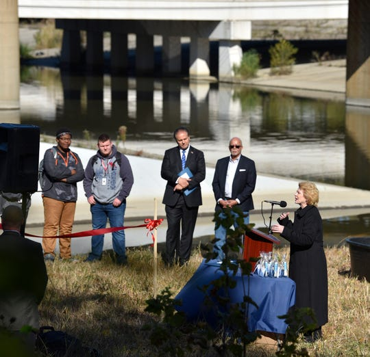 U.S. Sen. Debbie Stabenow, right, speaks from the podium as Wayne County Executive Warren Evans, center, and Wayne County Commissioner Sam Baydoun, left, listen in front of the Rouge River.