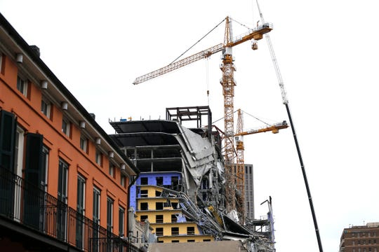 Workers in a bucket hoisted by a crane begin the process of preparing the two unstable cranes for implosion at the collapse site of the Hard Rock Hotel.