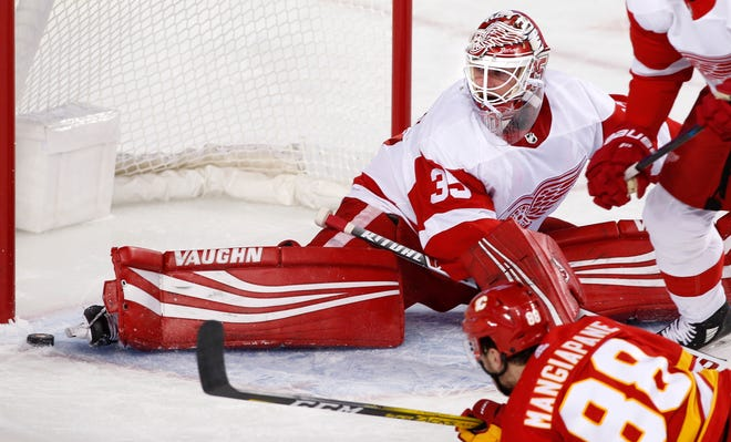 Red Wings goalie Jimmy Howard makes a toe-save against Flames left wing Andrew Mangiapane on Thursday.