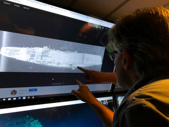 In this Wednesday, Oct. 16, 2019, photo, Vulcan Inc. director of subsea operations of the Petrel, Rob Kraft looks at images of the Japanese aircraft carrier Kaga, off Midway Atoll.