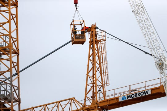 Workers in a bucket hoisted by a crane begin the process of preparing the two unstable cranes for implosion at the collapse site of the Hard Rock Hotel, which underwent a partial, major collapse while under construction in New Orleans.