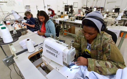 Seamstress Daynah Grant, right, of Southfield, and others sew together hockey jerseys.