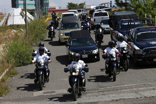 Police escort a caravan of funeral vehicles transporting the bodies of Mexican police officers killed in an apparent cartel ambush, in Morelia, Mexico, Tuesday, Oct. 15, 2019. The families of the 13 slain police officers gathered to mourn their loved ones outside a funeral home in the western state of Michoacan on Tuesday, many of them angry at the government and police chiefs they believe sent them to a certain death.