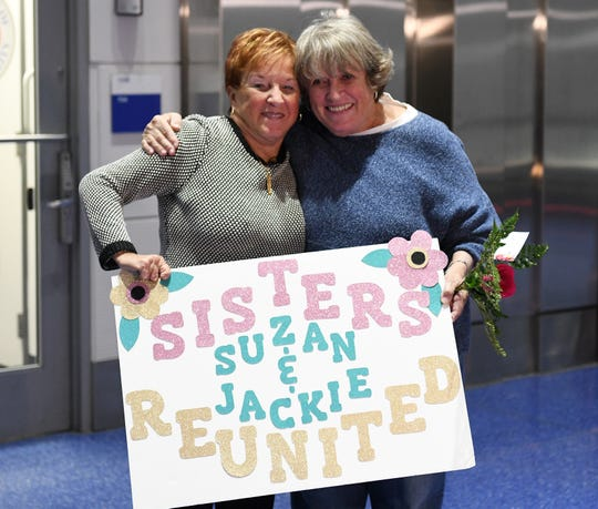 Sisters Jackie Murphy, 80, of Macomb Township, and Suzan Baekkelund, 76, of Nashville, hold a sign that Jackie's daughter Kelli made for the occasion.