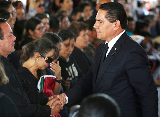 The governor of the Mexican state of Michoacan Silvano Aureoles shakes the hand of a relative of one of the Mexican police officers killed in an apparent cartel ambush, during a memorial service in Morelia, Mexico, Tuesday, Oct. 15, 2019.