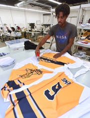 Trimmer Donta James, of Livonia, uses electric sizzors to trim away excess fabric before these hockey jerseys are sewn together.