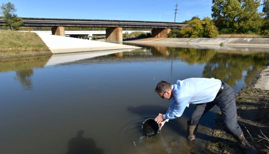 Environmental Consulting & Technology, Inc. senior scientist Marty Boote releases bluegill in the Rouge River near the Eagle Lane bridge at The Henry Ford for the Great Lakes Restoration Celebration, Friday, October 18, 2019.