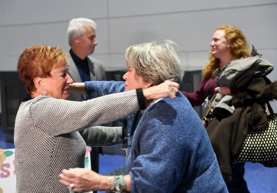 Jackie Murphy, left, and her sister, Suzan Baekkelund, hug each other, meeting face to face for the first time in 75 years, while, in background, Suzan's daughter, Inga Baekkelund, meets Jackie's son, Richard LeBlanc, at Detroit Metropolitan Airport.