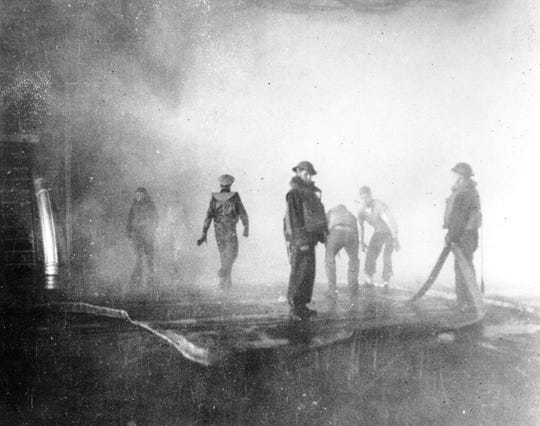 In this June 4, 1942 file photo crewmen aboard the USS Yorktown battle fire after the carrier was hit by Japanese bombs, during the Battle of Midway. Later the vessel had to be abandoned and was sunk by a Japanese submarine torpedo hit.
