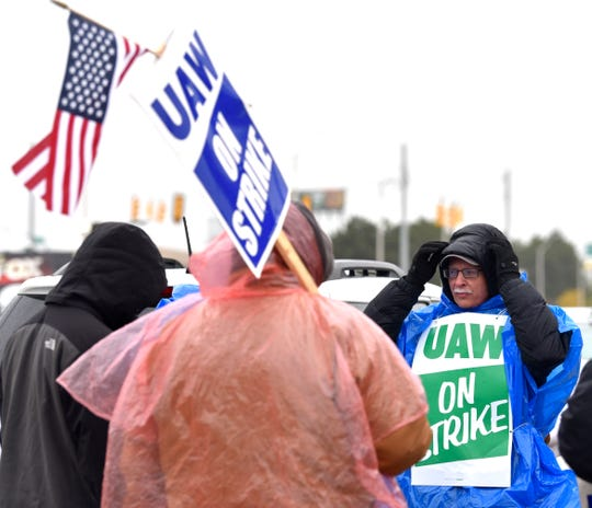 Detroit-Hamtramck Assembly paint-shop repair worker Scott Ferguson, right, of Dearborn on the picket line Wednesday as he learns a tentative deal may be reached.