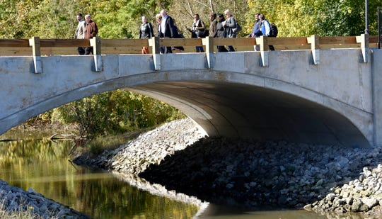 VIPs walk across the Eagle Lane bridge over a side channel of the Rouge River en route to the fish-release event.