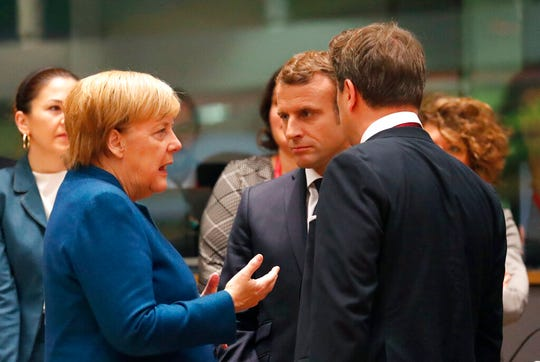 German Chancellor Angela Merkel, left, speaks with French President Emmanuel Macron, center, and Luxembourg's Prime Minister Xavier Bettel, right, during a round table meeting at EU summit in Brussels, Friday, Oct. 18, 2019.