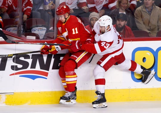 Red Wings center Darren Helm (43) uses his stick to slow down Flames center Mikael Backlund on Thursday.