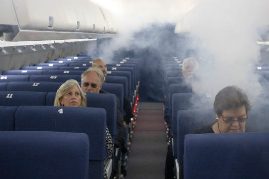FAA employees participate in a demonstration of an airline cabin filling with smoke, in a simulator at the FAA Civil Aerospace Medical Institute in the Mike Monroney Aeronautical Center, Thursday, Oct. 17, 2019, in Oklahoma City. Federal researchers, using 720 volunteers in Oklahoma City, will test whether smaller seats and crowded rows slow down airline emergency evacuations.