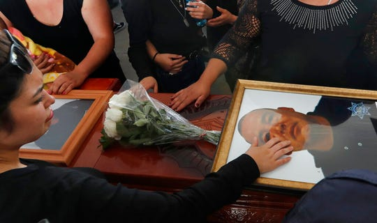 Relatives touch the coffin and photo of police officer Pablo Sergio Reynel, one of a group of officers killed in the line of duty, during a memorial service at the public security department headquarters for Michoacan, in Morelia, Mexico, Tuesday, Oct. 15, 2019.