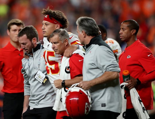 Quarterback Patrick Mahomes (15) of the Kansas City Chiefs is escorted off the field after a knee injury in the first half Thursday against the Denver Broncos.