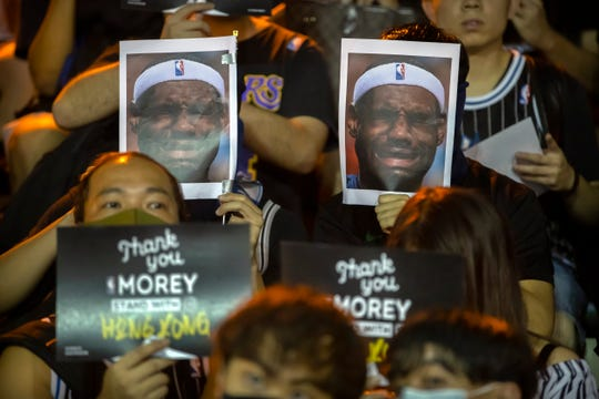 Demonstrators hold up photos of LeBron James grimacing during a rally at the Southorn Playground in Hong Kong, Tuesday, Oct. 15, 2019. Protesters in Hong Kong have thrown basketballs at a photo of LeBron James and chanted their anger about comments the Los Angeles Lakers star made about free speech during a rally in support of NBA commissioner Adam Silver and Houston Rockets general manager Daryl Morey.