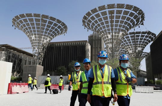 In this Oct. 8, 2019, photo, technicians walk at the three thematic districts at the under construction site of the Expo 2020 in Dubai, United Arab Emirates.