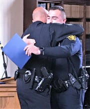 Sgt. Frank Hillman of the Elmira Police Department, left, hugs his son Tristan during a graduation ceremony Friday for the Elmira Chemung Regional Law Enforcement Training Center. Tristan Hillman was one of 12 recruits to graduate from the center.