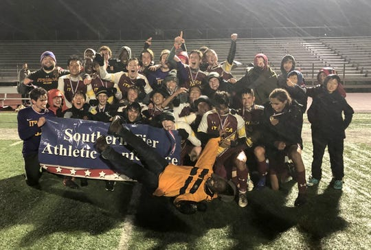 Ithaca head coach Gilbert Antoine rolls on the ground in front of his team during its postgame photo after a 1-0 win over Oneonta in the STAC boys soccer championship game Oct. 17, 2019 at Ithaca High School.