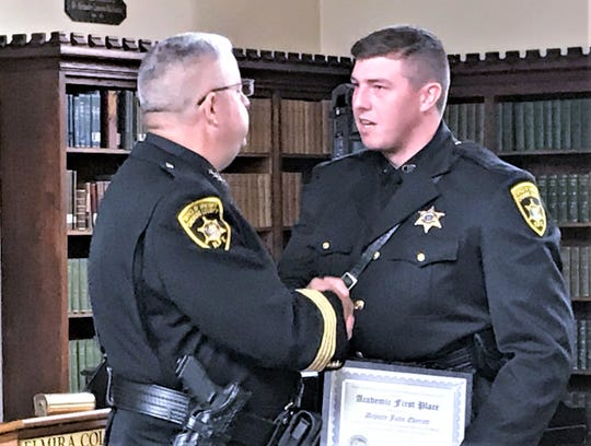 Chemung County Sheriff Bill Schrom, left, congratulates Deputy John Everett for earning academic first place from the Elmira Chemung Regional Law Enforcement Training Center.