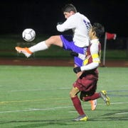 Aidan Mackey of Oneonta kicks the ball ahead in front of Ithaca's Terry Paw during Ithaca's 1-0 win in the STAC boys soccer championship game Oct. 17, 2019 at Ithaca High School.