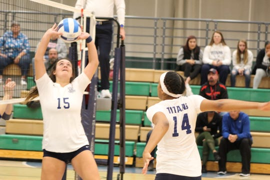 Terra State Community College setter Cassie Hoover (15) sets up teammate Jakyla Jackson (14) for a kill Thursday in the Titans three-set win over visiting Henry Ford College.
