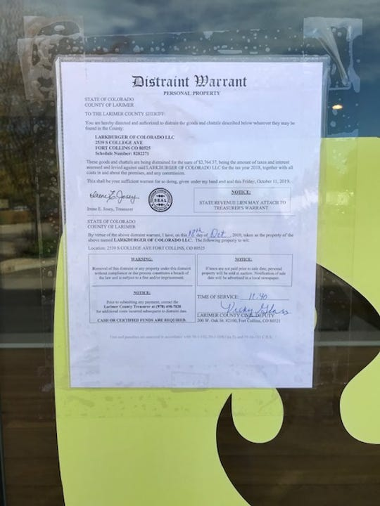 A sign inside Larkburger shows the burger restaurant owes Larimer County more than $2,000 in unpaid taxes from 2018.