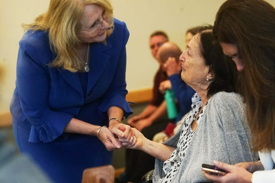 Assistant State Attorney Cynthia Ross greets Mary Ann Groves after Thomas Coyne, a medical examiner, testified in the trial of Jimmy Rodgers. Groves is the mother of Teresa Sievers.