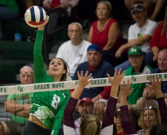 Isabella Perry of Fort Myers hits over Riverdale blockers in the Class 6A-District 8 volleyball championship game on Thursday, October 17, 2019, at Fort Myers High School.