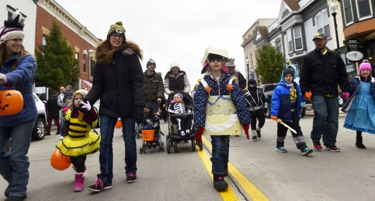 """Costumed children and parents march along North Third Avenue in the costume parade that's part of the annual """"Thrills on Third'' Halloween celebration in Sturgeon Bay."""