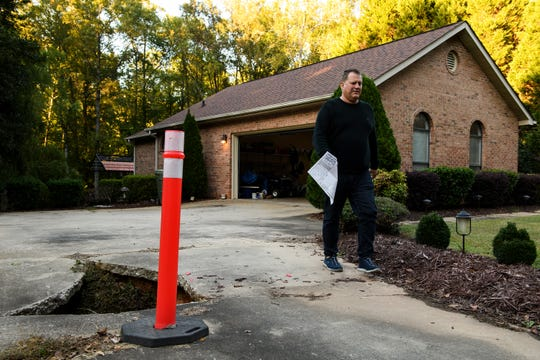 Russ Maio of Mauldin walks past a sinkhole in his driveway he says was caused by a city stormwater pipe Thursday, Oct. 17 ,2019. Maio says he has struggled getting the city to pay for stormwater damages on his property.