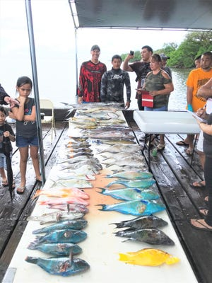 Todd Genereux and Robert Quintanilla, show at rear in long sleeves, display their winning catch at the 2018 Malesso Fiestan Tasi/Water Festival Spearfishing Competition.