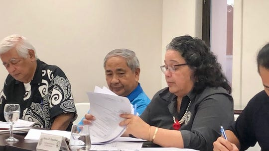 Guam Election Commission Executive Director Maria Pangelinan goes over reports while commissioners look on during an Oct. 17, 2019, meeting.