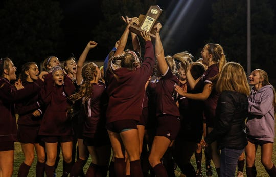 Henderson County's team raises the championship trophy after winning the Second Region Tournament with a 3-0 victory over University Heights in Thursday's final at the Stadium of Champions.