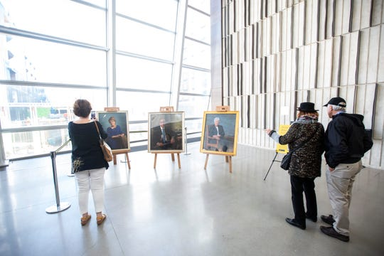 Spectators take photos of portraits of former UI presidents during the 'Future of Public Higher Education at America's Leading Research Universities' featuring former presidents, Friday, Oct., 18, 2019, at Voxman Music Building on the University of Iowa campus in Iowa City, Iowa.