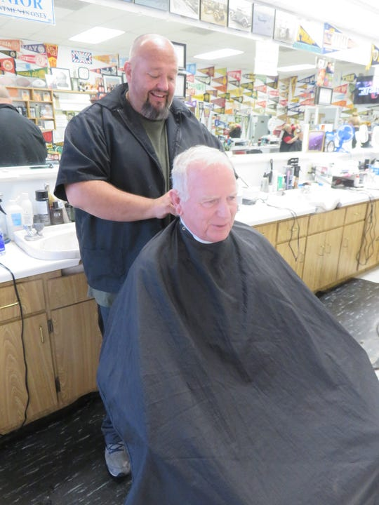 Rusty Manis cuts longtime customer and friends Bud Lamb's hair on Oct. 16.