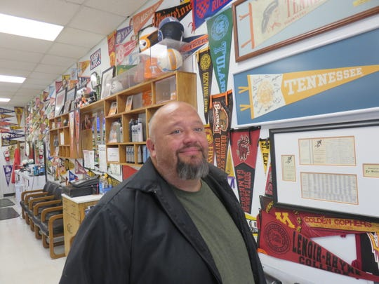 Rusty Manis stands in his pennant-lined Western Plaza Barber Shop.