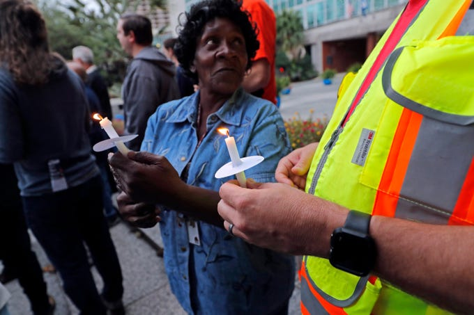 People hold candles during a candlelight vigil outside city hall for deceased and injured workers from the Oct. 12 Hard Rock Hotel construction collapse in New Orleans, on Thursday, Oct. 17. The vigil was organized by various area labor groups. (AP Photo/Gerald Herbert)
